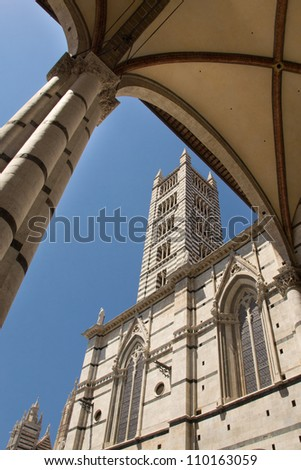 The Duomo di Siena (Siena cathedral) under a blue sky in the summer. - stock photo