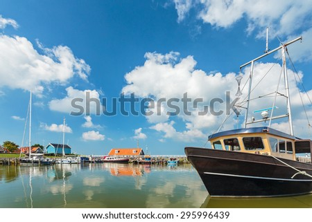 The Dutch harbor of Hindeloopen with a fishing boat in front - stock photo