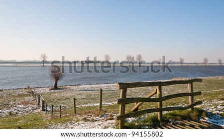 The Dutch river Bergsche Maas in winter. The first snow has fallen. In the foreground a wooden fence and a part of a cattle grid.