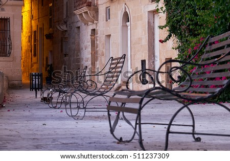 The early moning on the waterfront of Senglea city (or Civitas Invicta).  The view of the Triq is-Sirena street with the openwork forged metal benches in the sunrise light. Malta