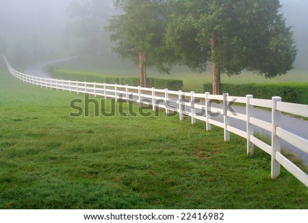 The early morning mist rises on a rural landscape. - stock photo