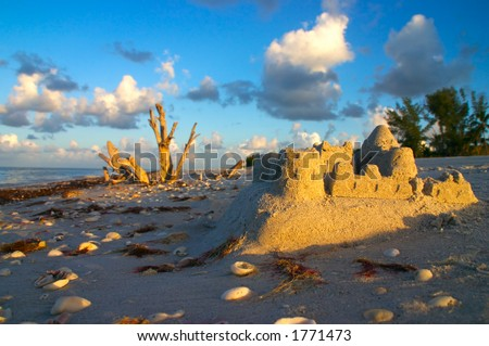 The early morning sun greets a leftover sandcastle - stock photo