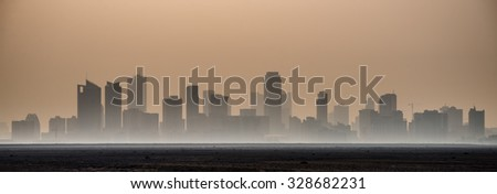 The early morning sun silhouettes the high-rise towers of the Seef district of Manama, Bahrain and creates a haze across the desert in this panoramic view. - stock photo