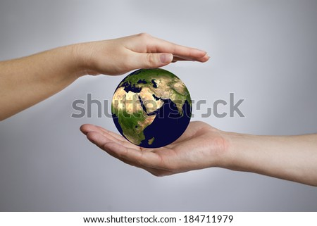 The Earth in a female and male hands. Gray background. 3D render. Elem ents of this image furnished by NASA - stock photo
