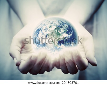 The earth shines in young woman hands. Concepts of save the world, protection, taking care, environment. Elements of this image furnished by NASA - stock photo