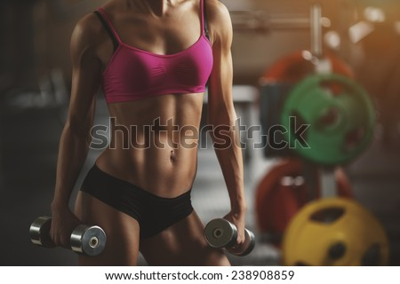 The effect of oil paints. Beautiful athletic woman shakes her abdominal muscles. Part of body - stock photo
