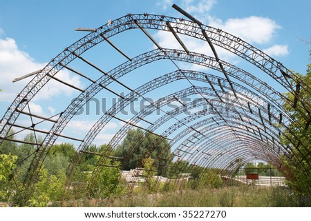 The effects of the financial crisis - an abandoned farm greenhouse. Beautiful sky - stock photo