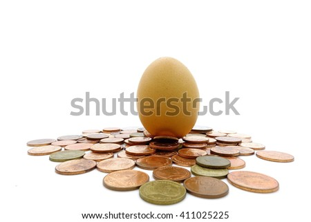 The egg are over many thai baht coins on a white background:select focus with shallow depth of field:Macro shot. - stock photo