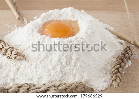 The egg in the flour surrounded by wheat, on the kitchen table. - stock photo