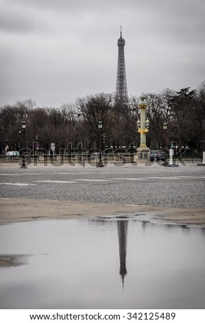 The Eiffel Tower and his reflection in a puddle as seen from the Concorde Square in Paris, France. Winter season. - stock photo