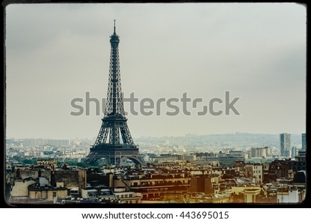 The Eiffel Tower in Paris, France. Vintage look with film grain, darkroom style frame, and light leak. - stock photo