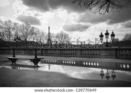 The Eiffel Tower reflecting in a puddle, a bench and an old street lamp in Jardin des Tuileries - stock photo