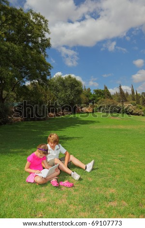 The elder brother taught her younger sister to play the computer. They sit in a park on the green grass - stock photo