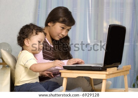 The elder sister and the junior brother play on a computer.