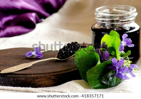 The elderberry jam in an open jar, a spoon and a bouquet of violets on the table - stock photo