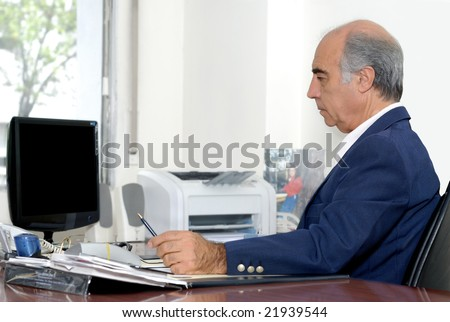 The elderly businessman on a workplace