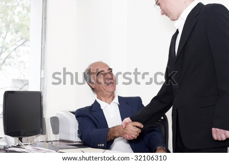 The elderly businessman with young colleague on a workplace - stock photo