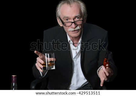 The elderly man with a glass of whisky on a black background
