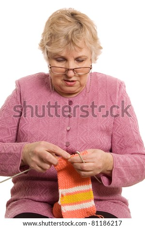 The elderly woman knits isolated on white