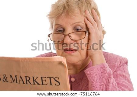 The elderly woman reads the newspaper - stock photo