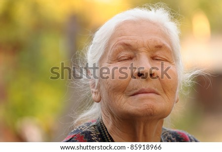 The elderly woman with closed eyes. A photo outdoors - stock photo
