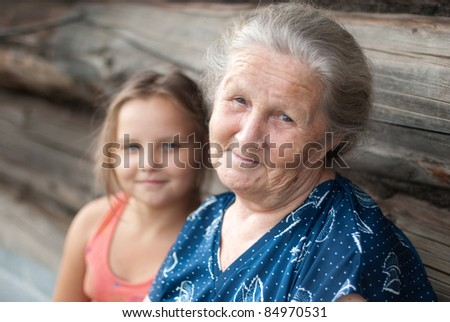 The elderly woman with the grand daughter against the wooden house - stock photo