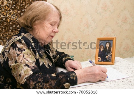 The elderly woman writes the letter to relatives - stock photo