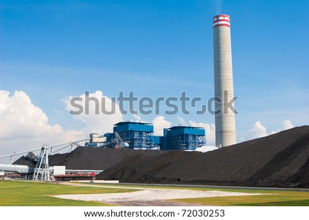 The electric generator power plant behind the mass of charcoal in a green site - stock photo
