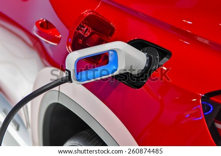 the electric vehicle charging cable inserted in plug - stock photo