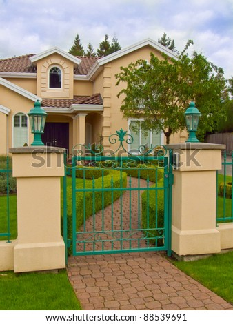 The elegant house and the entrance with beautiful front yard landskape - stock photo