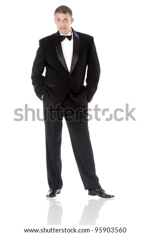 The elegant man in a classical tuxedo on a white background