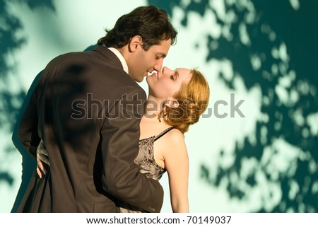 The embracing couple standing in front of a green wall and looking to each other - stock photo