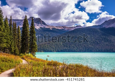 The Emerald Lake surrounded by coniferous forest  in the Rocky Mountains of Canada. Group of tourists crosses the lake in a rowboat - stock photo
