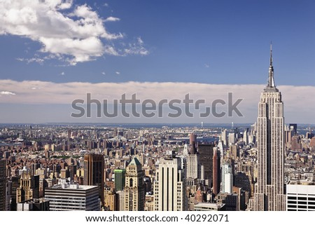 The Empire State Building rises above the Chelsea and the Garment District, Lower Midtown all the way to Lower Manhatten of New York City. - stock photo