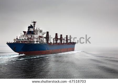The empty cargoship going through passage Dardanelless, Turkey, in rainy weather - stock photo