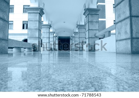 the empty hall of a very large high school building, blue tone. - stock photo