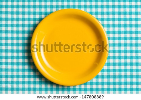 the empty plate on checkered tablecloth - stock photo