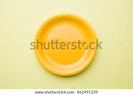 The empty yellow plate on color background.