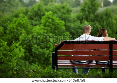 The enamoured couple sits on a bench against green trees - stock photo