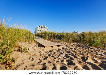 The end of a boardwalk onto a Maine beach, early morning - stock photo