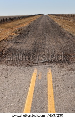 the end of the paved road where it turns into a gravel road extending to the horizon - stock photo