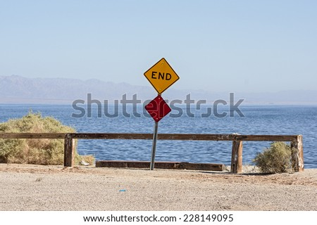 the end of the road where a road dead ends into the Salton Sea with a sign and barrier - stock photo