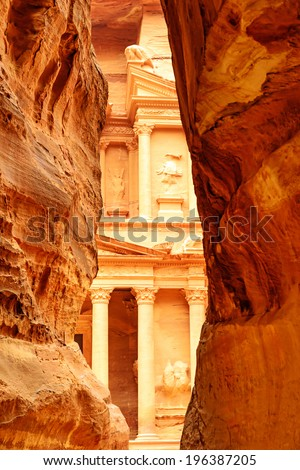 The end of the Siq, with its dramatic view of Al Khazneh in the ancient Jordanian city of Petra, Jordan.  It is known as The Treasury. Petra has led to its designation as a UNESCO World Heritage Site. - stock photo