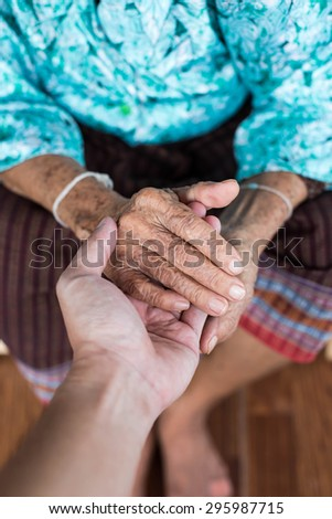 The engagement of young hand touches and holds an old wrinkled hand - stock photo