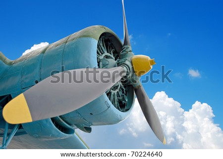 The engine of the old plane against blue cloudy sky - stock photo