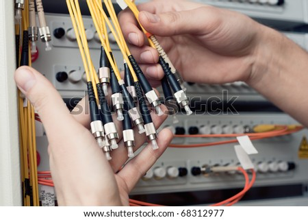 The engineer in a data processing center of ISP Internet Service Provider hold fiber patch cords - stock photo