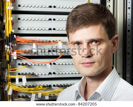 The engineer in a data processing center of ISP Internet Service Provider stand near fiber optic cross box. - stock photo