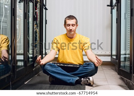 The engineer siting in datacenter near telecomunication equipment and relax