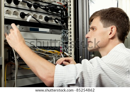 The engineer stand in datacenter near telecommunication equipment and looking at ethernet path cord.