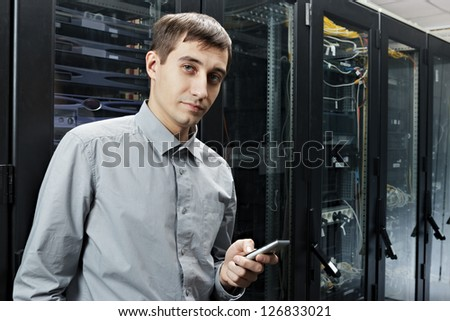 The engineer stand in datacenter near telecomunication equipment with smartphone. - stock photo